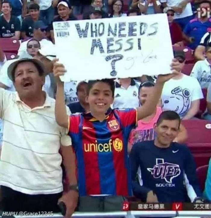 The boy is holding a board with the text: Who needs Messi?